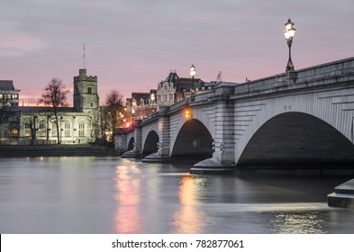 Putney Bridge, a busy traffic and pedestrian bridge over the River Thames in London during early evening.