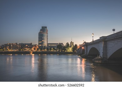Putney bridge connecting Fulham and Putney. Glossy River thames during the sunset