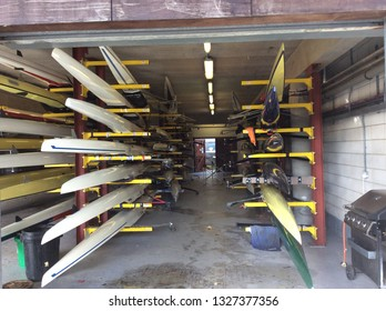 Putney London May 2018. Looking into the boathouse of Imperial College London showing single skull boats on several racks awaiting use. Bows pointing outwards hulls upside down.
