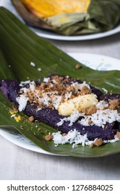 puto bumbong or purple steamed rice with shaved coconut meat and muscuvado sugar