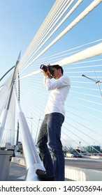 PUTRAJAYA BRIDGE, MALAYSIA - 21 MAY 2019 : A Photographer is standing while holding the camer.