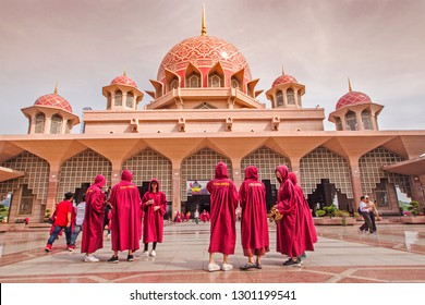 PUTRAJAYA MALAYSIA -14 JANUARY 2019: Travellers wearing islamic red dress code visits Pink Mosque in Putrajaya.