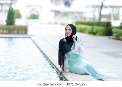 Putrajaya, Malaysia – April, 2019: A fashion portrait of a young and attractive Muslim Malay woman in the city.