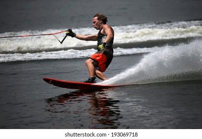 PUTRAJAYA, MALAYSIA - APRIL 26, 2014: Jarno de Lacy of New Zealand rides the waves at the Slalom Open event at the Putrajaya Nautique Ski & Wake Championship 2014.