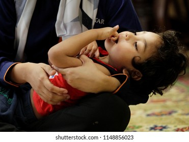 PUTRAJAYA, MALAYSIA - AUGUST 02, 2018. A toddler who is suffering from a seizure, known as Lennox-Gastaut syndrome at home in Putrajaya, Malaysia. Low light and high ISO photography.