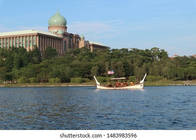 Putrajaya, Malaysia. August 12, 2019 : Perahu Dondang Sayang is cruising at Putrajaya Lake with Malaysia Prime Minister Office at background. This sightseeing service is using Malay traditional boat