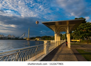 Putrajaya, Malaysia - Circa June 2018 - A perspective shot of Putrajaya Lake with pedestrian walkway and surrounded buildings in the background