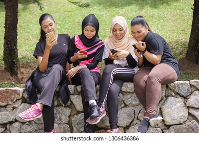 Putrajaya, Malaysia - Feb 2019 : A group of young Asian women use their cell phones while sitting and resting after jogging in the park.