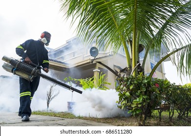 PUTRAJAYA, MALAYSIA - JULY 29, 2017 : Unidentified pest control operator from Ministry Of Helath Malaysia fogging to eliminate mosquito for preventing spread dengue fever and zika virus.