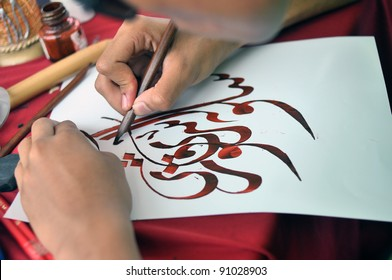 PUTRAJAYA, MALAYSIA - JULY 9: A student participates in arabic calligraphy  design contest at Malaysia's premier outdoor garden and flower showcase on July 9, 2010 in Putrajaya, Malaysia.
