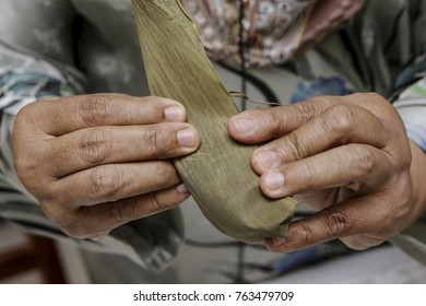 PUTRAJAYA, MALAYSIA - JUNE 09, 2013. Hands of Sapinah Ahmad showing how to wrap traditional halal Chinese homemade sticky rice dumpling, Bak Chang at her home in Putrajaya.