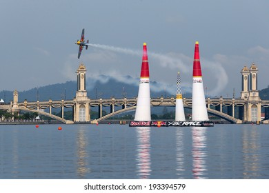 PUTRAJAYA, MALAYSIA - MAY 17, 2014: Peter Busenyei from Hungary flies his Corvus Racer 540 plane through the race course during the qualifying session of the Red Bull Air Race World Championship 2014.