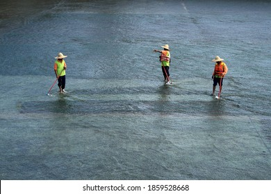 PUTRAJAYA, MALAYSIA - NOV 17: Unidentified labourers are cleaning the floor of the Putrajaya Dam on November17, 2009 in Putrajaya, Malaysia