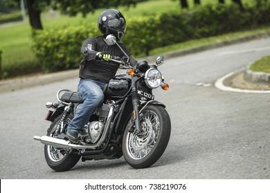 PUTRAJAYA, MALAYSIA - OCTOBER 20, 2017. A rider rides a Triumph Bonneville T120 motorcycle in Putrajaya.