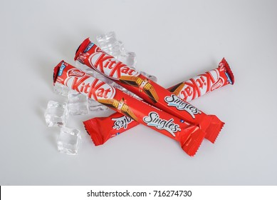 PUTRAJAYA, MALAYSIA - SEPTEMBER 14th, 2017 : Coca Cola classic or klasik drink with a cube of ice and a Kit Kat Chocolate on white isolated background.