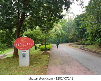 Putrajaya, Malaysia. September 29, 2018. Local taking a brisk walk in a park passing a signage of Putrajaya Seafood Restaurant at Taman Botani Putrajaya.