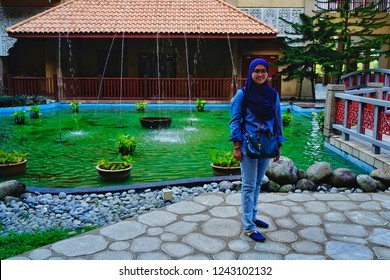 Putrajaya,Malaysia- November 24th,2018:A woman standing in front of a lake with a fountain in the Pullman Putrajaya Lakeside hotel. This is one of the best 5 star hotel in Malaysia.