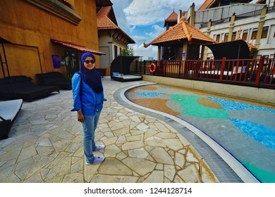 Putrajaya,Malaysia- November 24th,2018:A woman standing beside a swimming pool in the Pullman Putrajaya Lakeside hotel. This is one of the best 5 star hotel in Malaysia.