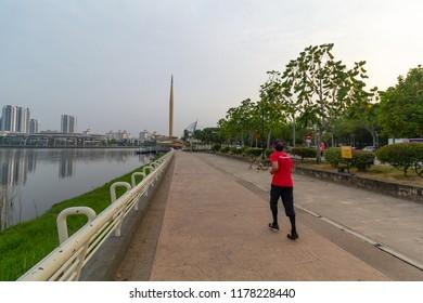 PUTRAJAYA,MALAYSIA-AUGUST 3 2018:A man wears red shirt jog in the morning hour at Millenium Park of Putrajaya,Malaysia.