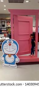 PUTRAJAYA,MALAYSIA-MAY 20,2019: A little cute girl standing in front of Doraemon mascot .