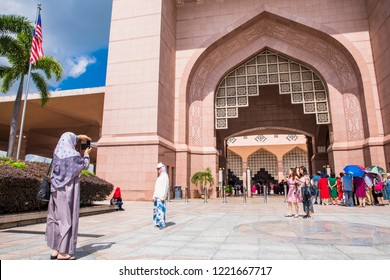 PUTRAJAYA,MALAYSIA-OCTOBER 15,2018: Islamic tourists taking photo in front of Putra Mosque, Is a landmark of Putrajaya and one of the most modern mosques in the world.