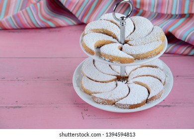 Putri Salju or crescent-shaped cookies coated with powdered sugar, arrange on cake stand on pink background. Traditional Indonesian cookies to celebrate Eid al Fitr, Festival of Breaking the Fast.