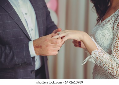 Puts a ring on the bride's hand . Groom puts wedding ring on bride's hand in church .Man puts a wedding ring on a bride's hand, close-up photo