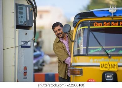 PUTTAPARTHI, ANDHRA PRADESH/INDIA - November 06 /2016: Indian driver of local taxi stay and smiling next petrol station.