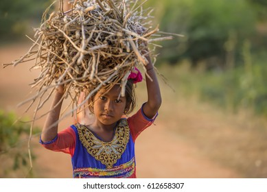 PUTTAPARTHI, ANDHRA PRADESH/INDIA - October 23, 2016: Indian girl carrying wood on head at the road. Child Labor. Copy space.