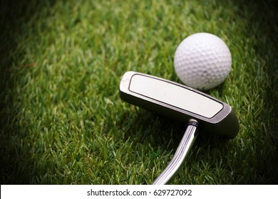 Putter and golf ball on green grass