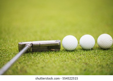 Putter and golf balls on the golf course with the green grass