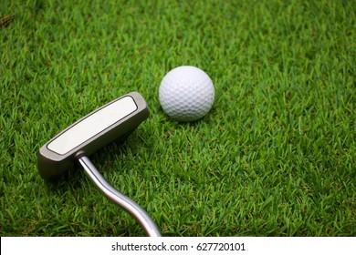 Putter with golf balls on green grass