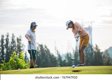 putter in hands of woman player putt follow through the hole on green in golf course, the golfmate force looking in background