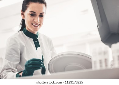 Putting analyses in place. Portrait of cheerful skilled doctor holding a test tube in hand while smiling and looking at it