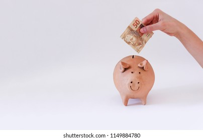 Putting Brazilian money in pig coin isolated on white background
