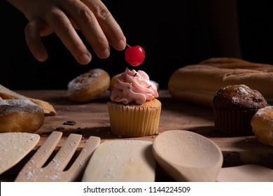 Putting a cherry on a top of pink cup cake among its ingredients with dark background, wooden spoon and fork.