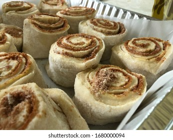 Putting cinnamon rolls into baking pan to be baked in the oven.