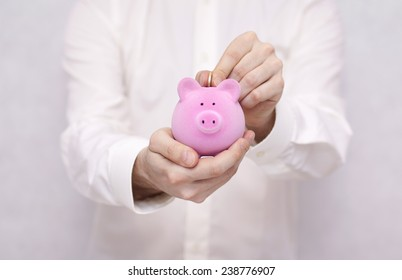 Putting coin into the piggy bank