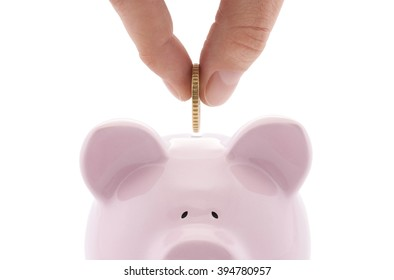 Putting coin into the piggy bank isolated on white background