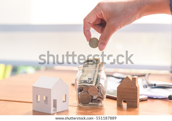 putting coins concept of banking near house of the miniature , finance and savings.