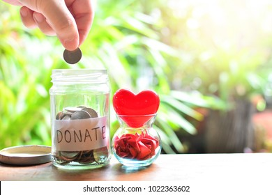 putting coins money in donate glass bottle for concept charity and philanthropy donation