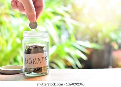 putting coins on donate glass bottle for concept charity and donation philanthropy