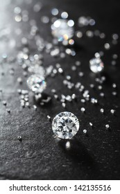 putting diamonds on the surface of the stone closeup. more diamonds out of focus in background