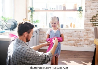 Putting gloves on. Father and daughter putting pink gloves on before cleaning kitchen at the weekend