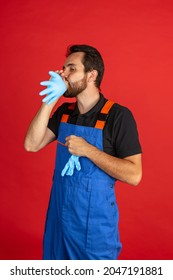Putting gloves on. Funny young bearded man, male auto mechanic or fitter wearing blue work dungarees isolated over red studio background. Concept of funny meme emotions, ad, job, insipation, ideas