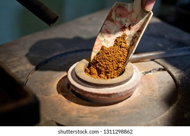 putting gold powder in showel into mettalurgical furnace for melt down