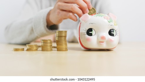 Putting golden coins into piggy bank at home
