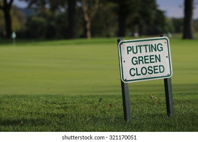 Putting Green Closed Golf Course Sign Positioned near Green, with A Golf Cart, Golfers, and New York City in the Background.