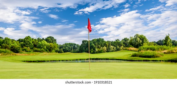 Putting green with a flag at a golf course on a summer day