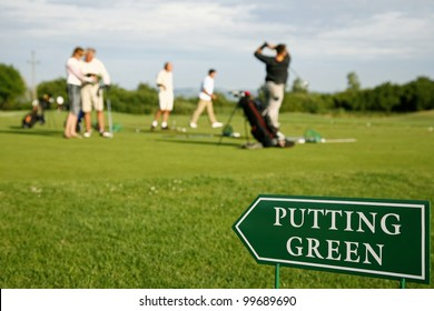 Putting green guidance board in the foreground and golf players out of focus on the background.